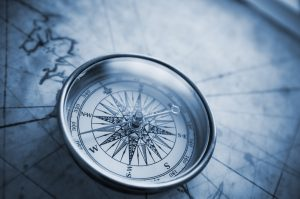 Compass on old map with blue tone.